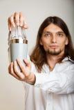 Hombre joven con la coctelera que hace que el cóctel bebe Fotos de archivo libres de regalías