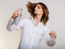 Hombre joven con la coctelera que hace que el cóctel bebe Imágenes de archivo libres de regalías