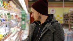 Hombre joven con la compra del carro de la compra en refrigerado en supermercado almacen de video