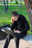 Hombre joven con la computadora portátil al aire libre Imagen de archivo libre de regalías