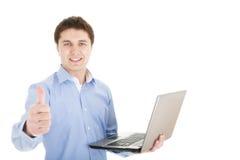 Hombre joven con la computadora portátil que muestra los pulgares para arriba Fotos de archivo libres de regalías
