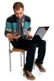 Hombre joven con la computadora portátil y el teléfono móvil Imagen de archivo libre de regalías