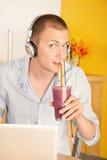 Hombre joven con la computadora portátil y los auriculares Fotos de archivo libres de regalías
