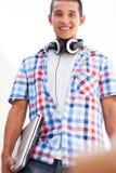 Hombre joven con la computadora portátil y los auriculares Imagen de archivo libre de regalías