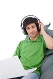 Hombre joven con la computadora portátil y los auriculares Imagenes de archivo