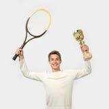Hombre joven con la estafa de tenis y la taza del ganador Fotos de archivo