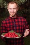 Hombre joven con la fruta del espino Imagenes de archivo