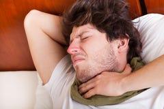 Hombre joven con la garganta dolorida Fotografía de archivo