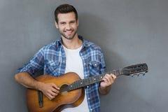 Hombre joven con la guitarra Foto de archivo libre de regalías