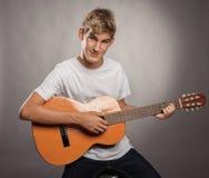 Hombre joven con la guitarra acústica Fotografía de archivo