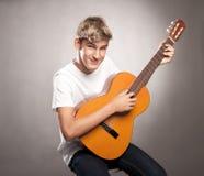Hombre joven con la guitarra acústica Foto de archivo