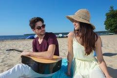 Hombre joven con la guitarra y la novia en la playa Fotografía de archivo libre de regalías