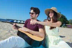 Hombre joven con la guitarra y la novia en la playa Imagen de archivo libre de regalías
