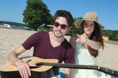 Hombre joven con la guitarra y la novia en la playa Fotos de archivo