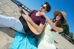 Hombre joven con la guitarra y la novia en la playa Fotografía de archivo