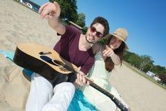 Hombre joven con la guitarra y la novia en la playa Imagenes de archivo
