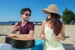 Hombre joven con la guitarra y la novia en la playa Foto de archivo