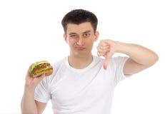 Hombre joven con la hamburguesa malsana sabrosa de los alimentos de preparación rápida Fotos de archivo libres de regalías
