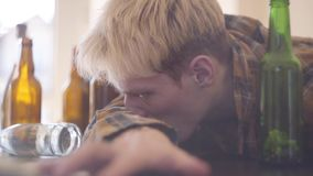 Hombre joven con la intoxicación de la droga y del alcohol Adolescencias preocupadas El foco est? en la jeringuilla C?mara lenta metrajes