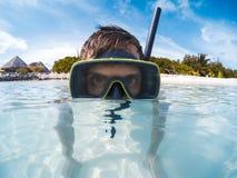 Hombre joven con la máscara del equipo de submarinismo en el agua azul clara que mira a la cámara fotos de archivo