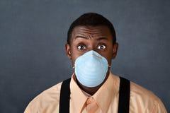 Hombre joven con la máscara quirúrgica Foto de archivo libre de regalías