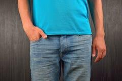 Hombre joven con la mano derecha en el bolsillo de sus tejanos, weari Foto de archivo libre de regalías