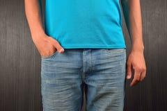 Hombre joven con la mano derecha en el bolsillo de sus tejanos, weari Fotos de archivo libres de regalías