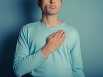 Hombre joven con la mano en su pecho Fotografía de archivo libre de regalías