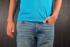 Hombre joven con la mano izquierda en el bolsillo de sus tejanos, wearin Fotografía de archivo libre de regalías