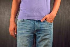 Hombre joven con la mano izquierda en el bolsillo de sus tejanos, wearin Foto de archivo libre de regalías