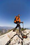 Hombre joven con la mochila en una montaña Fotos de archivo libres de regalías