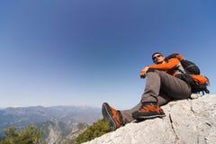 Hombre joven con la mochila en una montaña Fotos de archivo
