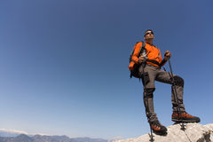 Hombre joven con la mochila en una montaña Fotografía de archivo libre de regalías
