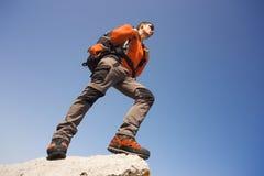 Hombre joven con la mochila en una montaña Imagen de archivo