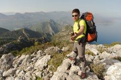 Hombre joven con la mochila en una montaña Fotografía de archivo