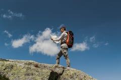 Hombre joven con la mochila grande que camina para alcanzar el top de la monta?a durante un d?a soleado Lectura de una correspond imagen de archivo