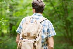 Hombre joven con la mochila que camina en bosque Fotos de archivo