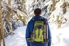 Hombre joven con la mochila que camina en bosque del invierno imagenes de archivo