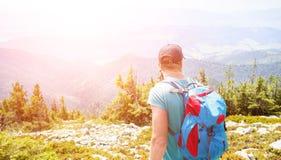 Hombre joven con la mochila que camina en las montañas Imagen de archivo libre de regalías
