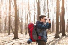 Hombre joven con la mochila que mira los prism?ticos, caminando en el bosque foto de archivo