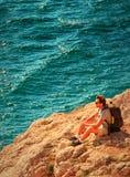 Hombre joven con la mochila que se relaja en el acantilado rocoso con el mar azul en fondo Fotos de archivo