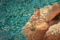 Hombre joven con la mochila que se relaja en el acantilado rocoso con el mar azul en fondo Imagen de archivo libre de regalías
