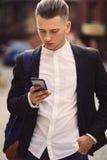 Hombre joven con la mochila que sostiene un teléfono Fotos de archivo