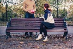Hombre joven con la mujer de la reunión del regalo en parque Imágenes de archivo libres de regalías