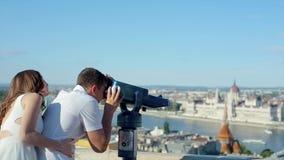 Hombre joven con la mujer en el punto de visión usando binocular de fichas para ver la belleza de la ciudad almacen de metraje de vídeo
