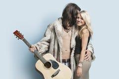 Hombre joven con la mujer feliz de abarcamiento de la guitarra contra fondo azul claro Fotos de archivo libres de regalías