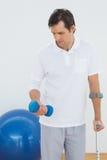 Hombre joven con la muleta y la pesa de gimnasia imagen de archivo libre de regalías