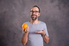 Hombre joven con la naranja Fotos de archivo libres de regalías