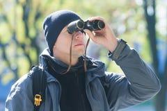 Hombre joven con la observación de pájaros de los prismáticos en el fondo natural de la demi-estación Fotos de archivo