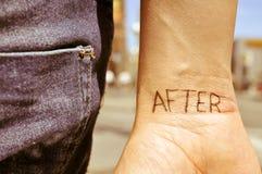 Hombre joven con la palabra después de tatuado en su muñeca Fotos de archivo